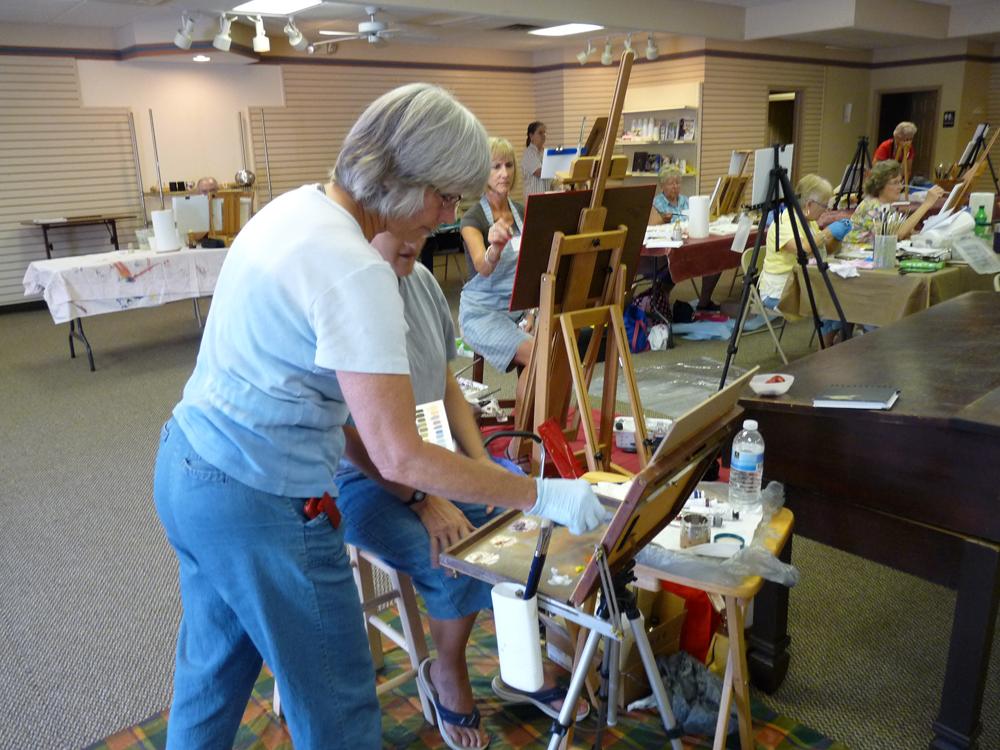 Carol Reesor helping a student match color mixes.